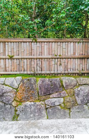 Bamboo fence on stone with green leaves