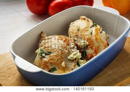 fried filled chicken breast fillet in Mediterranean style with feta cheese and herbs in a baking dish on a wooden kitchen board selected focus and narrow depth of field
