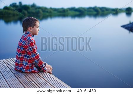 boy at dusk sits on the docks and looks afar. pensive boy in a plaid shirt sitting on a wooden pier near the water. side view. empty space for your text