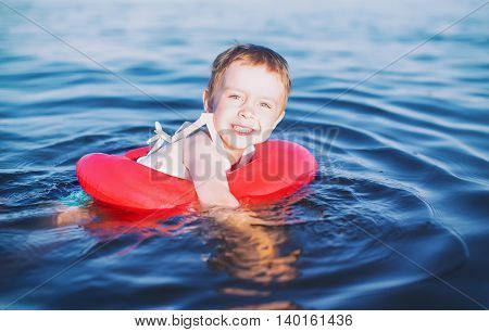 boy enjoys swimming with rubber ring. joyful child learns to swim with the training inflatable circle. the concept of children's safety on the water