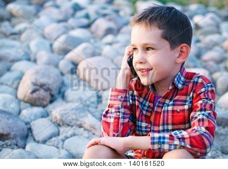 sharing feelings at a distance. kid happily smiling while talking on the phone. cute young boy calling on the phone on the beach. empty space for your text