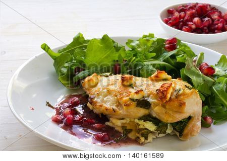 fried chicken breast fillet gratinated with feta cheese arugula salad and pomegranate sauce on a white wooden kitchen table selected focus narrow depth of field