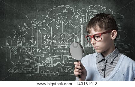 Cute boy looking through magnifying glass against blackboard background