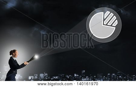 Young elegant businesswoman with flashlight and growth symbol in air