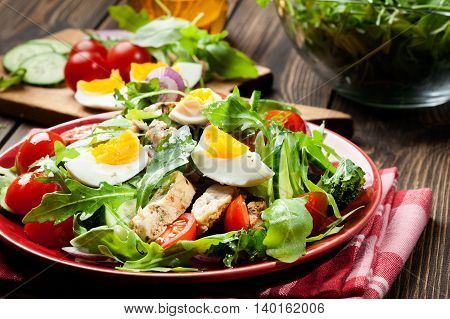 Fresh salad with chicken tomatoes eggs and arugula on plate. Healthy food