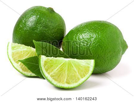 two limes with slices and leaf isolated on white background.