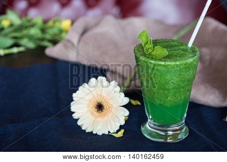 Healthy organic green smoothie with basil mint and lemon