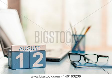 August 12th. Day 12 of month, wooden color calendar on IT office background. Summer time. Empty space for text.