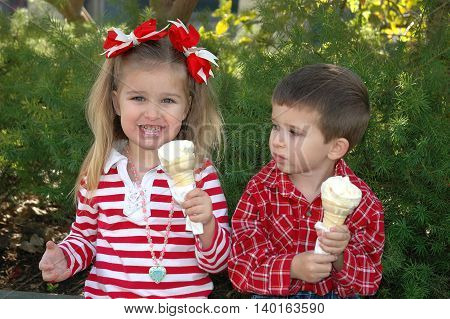three year old caucasian girl and four year old boy eating ice cream having fun on a cold December day in California