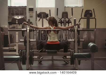 Young beautiful girl raises the bar in the gym