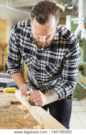 Hard working craftsman working with planer in a workshop for woodwork. Handsome man with tattoo and beard.