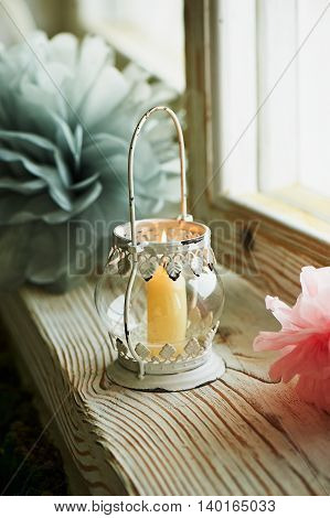 Holder white candle with Oriental ornaments with swirls, with a burning candle