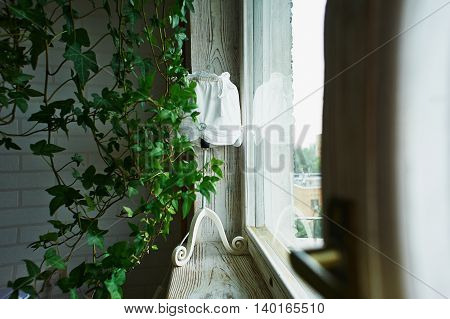 White lamp with fabric shade standing on a wooden window sill in the frame of the green plant