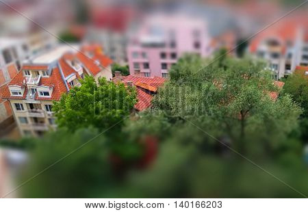 Cute toy like miniature tilt-shift effect photo of a residential housing top roof skylight windows and trees around the buildings