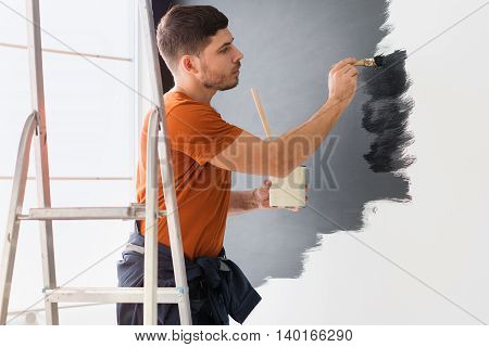 Man paints the wall in black standing on a stepladder.