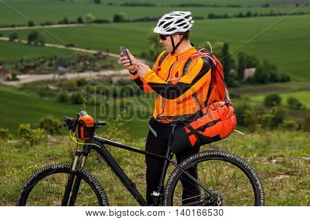 Handsome Young Man In Orange Shirt Stops Cycling, To Check His Phone on the Meadow against Blue Sky