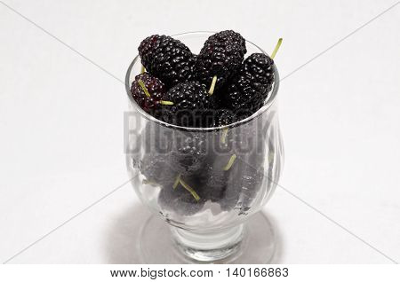 mulberries in a glass on a white background