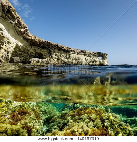View of the cliffs and sea caves of Cape Greco from under the water and above the water. Cyprus