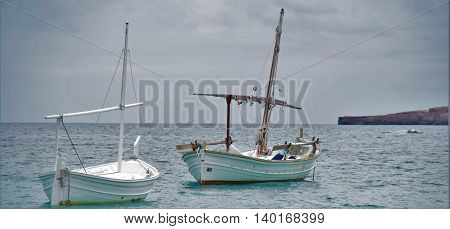 Two boats on the sea, approached aground