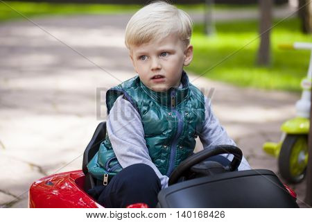 Blonde Little boy driving big toy car, spring outdoors