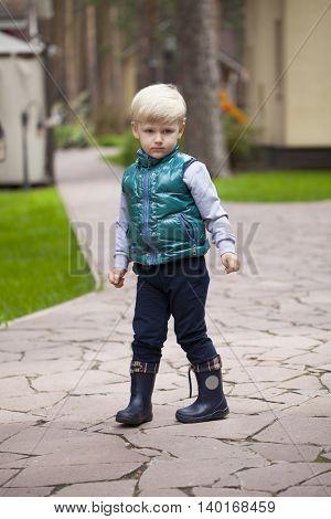 Full length of little blonde boy, spring outdoors