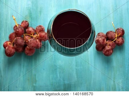 A vibrant photo of a glass of red wine with bunches of grapes shot from above on a turquoise blue wooden background texture with copyspace