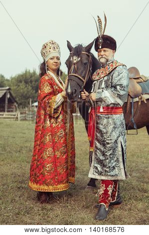 King And Queen Dressed In Medieval Clothes Are Standing With The Horse On The Rural Summer Backgroun