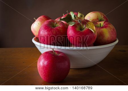 Honey crisp apples in a pottery bowl sitting on a wooden table.