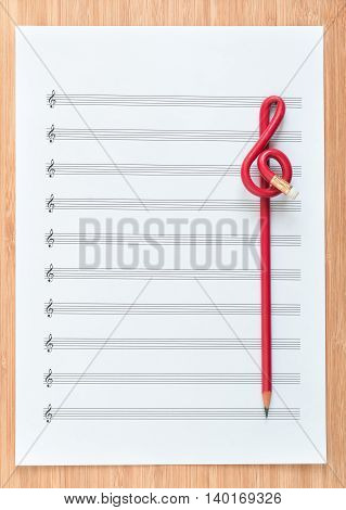 Blank sheet music end a red pencil in the shape of treble clef. Composing concept
