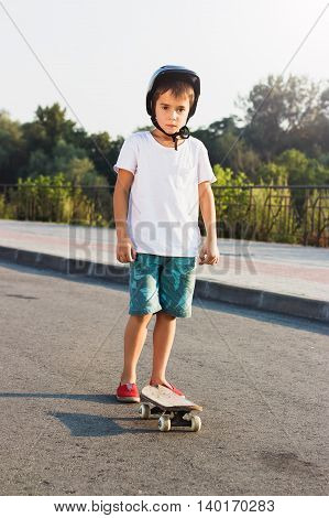 Boy Stands With A Skateboard Outdoors