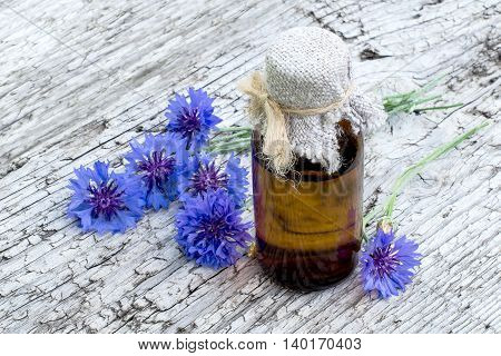 Medicinal plant Centaurea cyanus commonly known as cornflower and pharmaceutical bottle on old wooden table