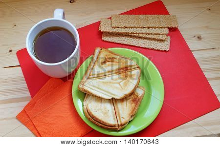 Breakfast on a red and wooden background. Crispbread sandwiches and cup of hot tea on the table - tasty meal.