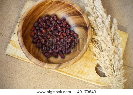 Dry briar in wooden plate. Dried rose hips and fluffy grass. Healthy resehip for brew.