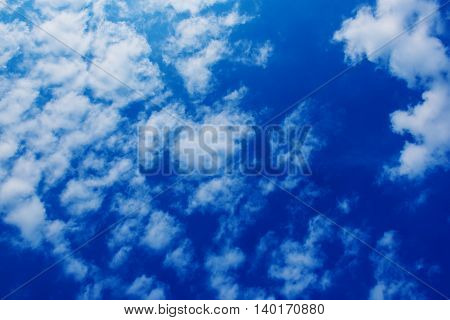 Blue sky with the fluffy white clouds, natural background with copy space