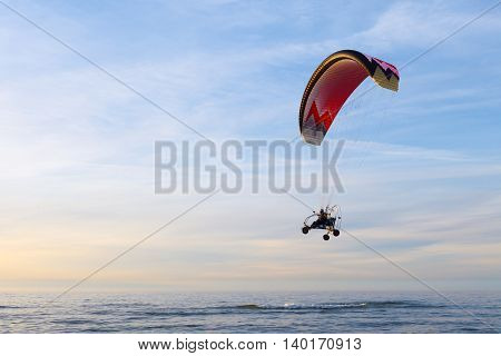 Motor Paraglider flying over the sea and the beach