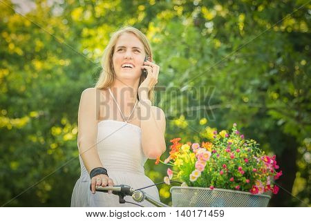 Portrait of pretty young female on retro bicycle with basket full of colorful flowers using smart phone. Summer, recreation and technology concepts.