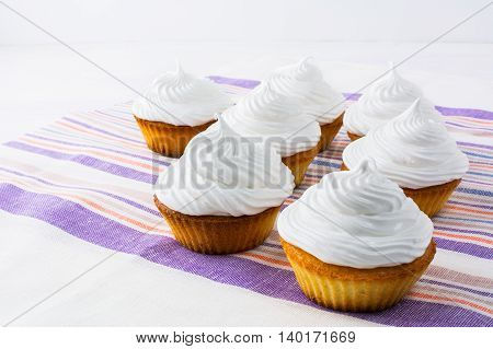 Row of white cupcakes on the striped linen napkin. Homemade cupcakes with whipped cream. Birthday cupcake.