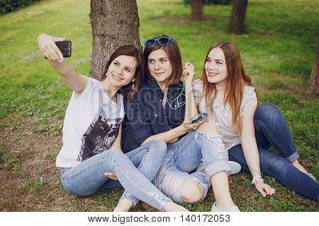 three beautiful girls in the park and take pictures on your phone
