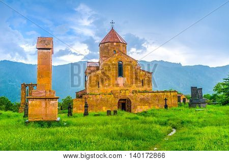 The medieval Basilica in Odzun village surrounded by the old cemetery and with the huge mountain range in the distance Alaverdi Armenia.