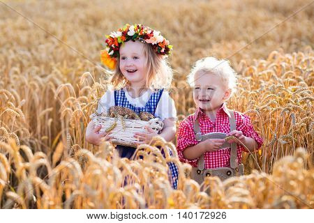 Kids in traditional Bavarian costumes in wheat field. German children eating bread and pretzel during Oktoberfest in Munich. Brother and sister play outdoors during autumn harvest time in Germany.