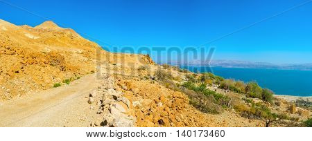 The road into the distance in the mountains of Judean Desert with the view on the Dead Sea Ein Gedi Israel.
