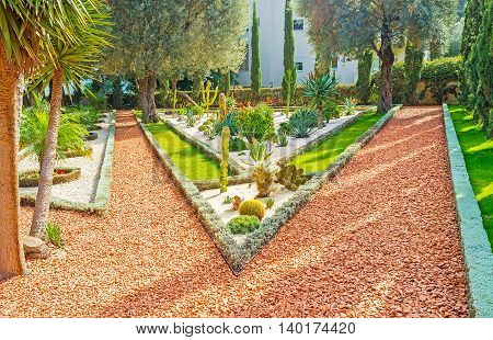 The flower bed includes many exotic cactuses growing among the white gravel Bahai Gardens Haifa Israel.