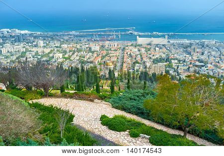 The greenery of Bahai Gardens with the city located at the Carmel Mountain foot Haifa Israel.