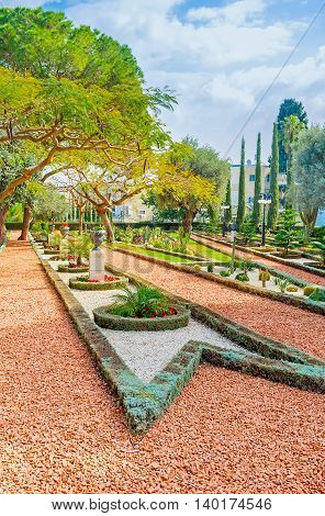 The beauty of ornamental garden with gravel paths trimmed plants and geometric flower beds Bahai Gardens Haifa Israel.