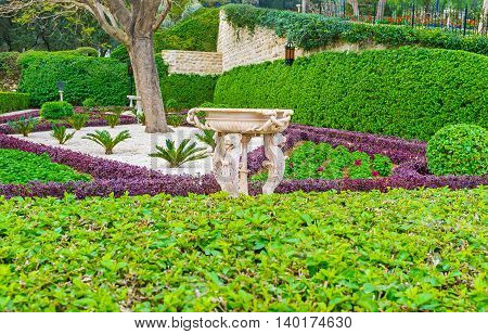 The white stone fountain decorated with the complex carvings among the greenery of Bahai Garden Haifa Israel.
