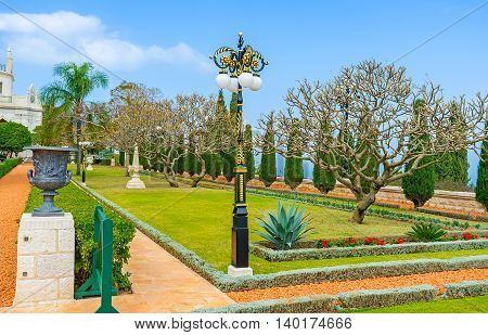 The Bahai Garden boasts beautiful park sculptures and old style streetlights along the alleys Haifa Israel.