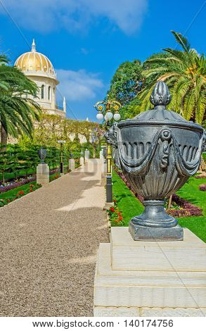 The black decorative urn on the stone column in Bahai Gardens with the golden dome of the Temple on the background Haifa Israel.
