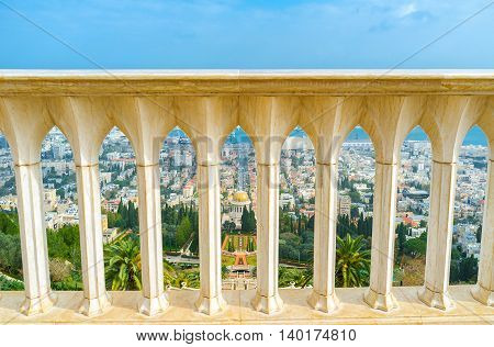 The view on Bahai Gardens and Shrine through the white stone handrail on the top of Carmel Mount Haifa Israel.