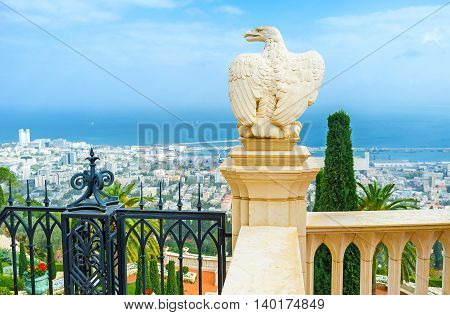 The white stone eagle guards the gate to Bahai Gardens and overlooks the cityscape and coast of Haifa Israel.