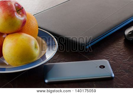 Apples and smart phone on the table next to the laptop. Healthy break